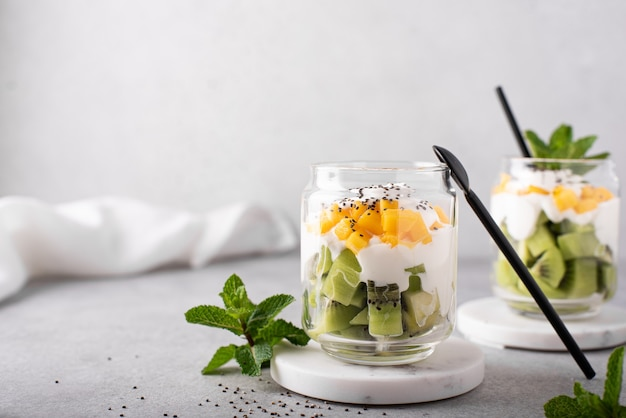 Homemade greek yogurt with kiwi and mango slices in a glass jar, close up