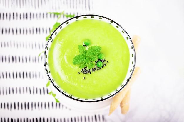 グリーンピース、ミントの葉、ブラッククミンまたはニゲラサティバとブレッドスティックを使った自家製グリーンクリームスープ