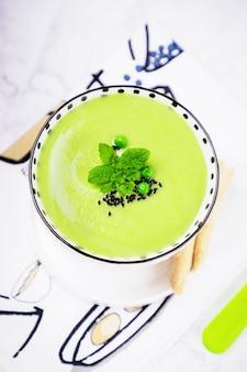 グリーンピース、ミントの葉、ブラッククミンまたはニゲラサティバを添えた自家製グリーンクリームスープ