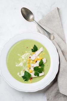 Домашний зеленый суп-пюре из брокколи, авокадо, курицы и кукурузы со сливками в деревенской керамической тарелке на белом бетоне
