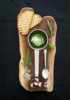 Homemade green spinach cream-soup in a metal scoop with grilled bread slices, herbs, spices on rustic wooden  serving board over black background