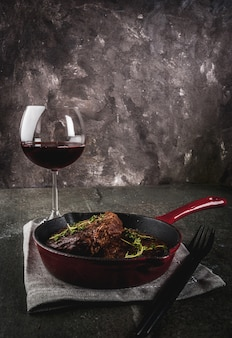 Homemade grilled beef steaks with thyme in a portioned frying pan, with a fork, knife and a glass of wine