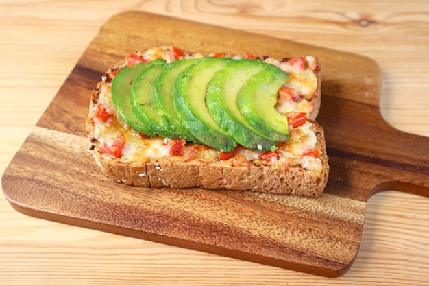 Homemade grilled cheese toast topped with tomato and sliced avocado on wooden breadboard