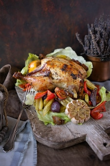 Homemade grilled chicken with vegetables and herbs on vintage wooden board