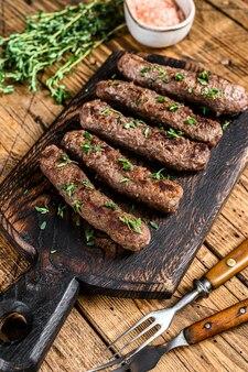 Домашние мясные колбаски на гриле лула-кебаб на разделочной доске