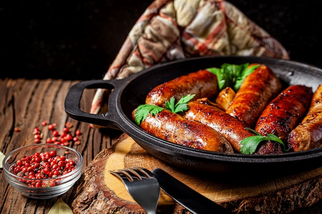 Homemade grilled pork barbecue sausages in an iron pan