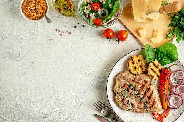 自家製グリルポークステーキ、野菜、スパイス、パルメザンチーズとコンクリートの背景