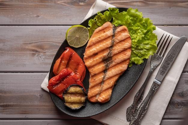 Домашний стейк из лосося на листьях салата на тарелке на льняной салфетке с ножом и вилкой