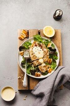 セラミックプレートにソース、ブロッコリー、ルッコラ、フダンソウを添えた自家製グリルターキーステーキ