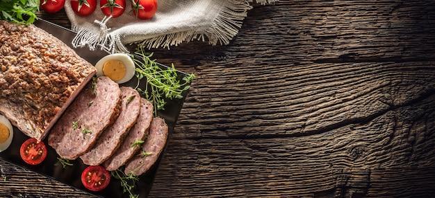 素朴なテーブルに卵トマトセロリハーブとタイムを添えた自家製挽き肉のミートローフ-上面図。