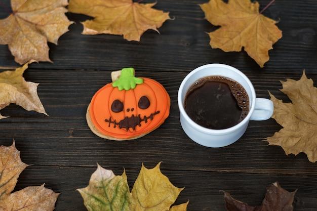 Самодельные тыква печенья хеллоуина и чашка кофе на деревянном столе с осенними листьями.