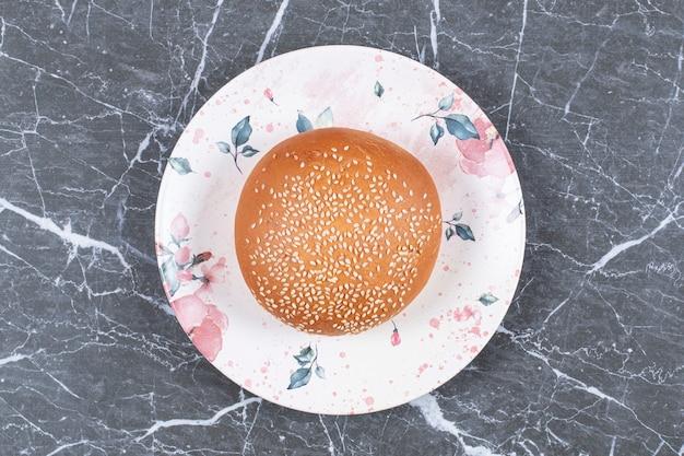 대리석 표면에 접시에 참깨와 함께 만든 햄버거 빵