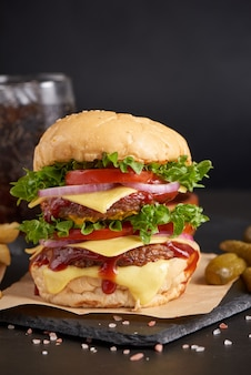 Homemade hamburger or burger with fresh vegetables and cheese lettuce and mayonnaise served, french fries on pieces of brown paper on black stone table . concept of fast food and junk food