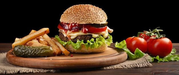 Крупный план домашнего гамбургера с говядиной, помидорами, салатом, сыром и картофелем на разделочной доске. фастфуд на темном фоне.