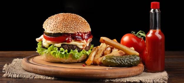 まな板の上に牛肉、トマト、レタス、チーズ、フライドポテトを添えた自家製ハンバーガーのクローズアップ。ハンバーガーに挿入された小さな白い旗。暗い背景のファーストフード。