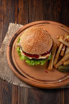 まな板の上に牛肉、トマト、レタス、チーズ、フライドポテトを添えた自家製ハンバーガーのクローズアップ。上面図。