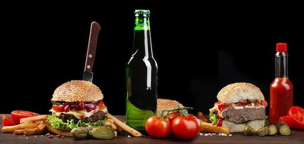 牛肉、トマト、レタス、チーズ、タマネギ、ソースボトルの木製テーブルと自家製ハンバーガーのクローズアップ。暗い背景のファーストフード。