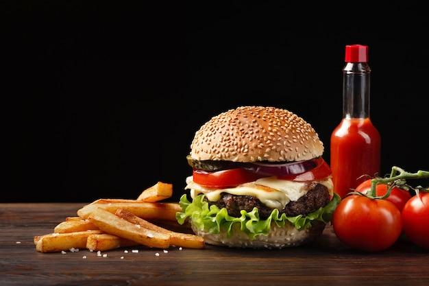 牛肉、トマト、レタス、チーズ、タマネギ、フライドポテトとソースボトルの木製テーブルと自家製ハンバーガーのクローズアップ。暗い背景のファーストフード。