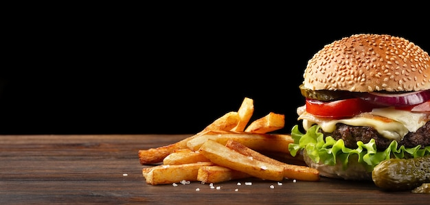 Homemade hamburger close-up with beef, tomato, lettuce, cheese, onion, french fries and sauce bottleon wooden table. fastfood on dark background.
