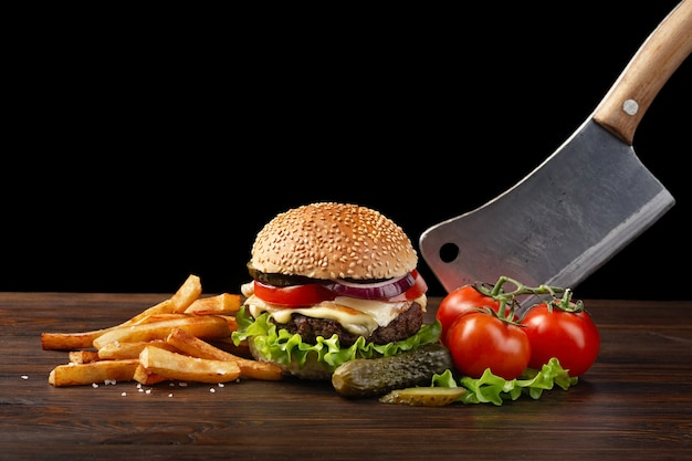 Homemade hamburger close-up with beef, tomato, lettuce, cheese, onion and french fries on wooden table. in the burger stuck a knife. fastfood on dark background with place for your text.