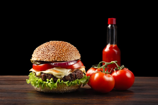 Homemade hamburger close-up with beef, tomato, lettuce, cheese and sauce bottle on wooden table. fastfood