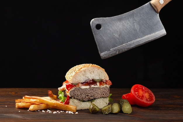 Homemade hamburger cut in half close-up with beef, tomato, lettuce, cheese and french fries on wooden table. meat cleaver in hand. fastfood on dark background.