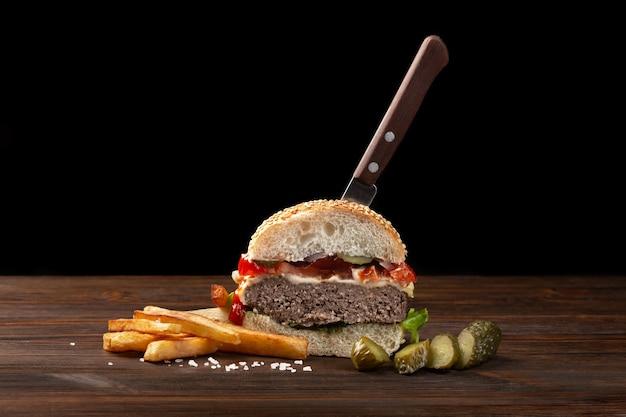 木製のテーブルに牛肉、トマト、レタス、チーズ、フライドポテトをクローズアップで半分に切った自家製ハンバーガー。ハンバーガーにナイフを刺した。暗い背景のファーストフード。