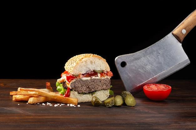 木製のテーブルに牛肉、トマト、レタス、チーズ、フライドポテトをクローズアップで半分に切った自家製ハンバーガー。手に肉切り包丁。暗い背景のファーストフード。