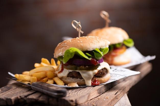 Домашний гамбургер или гамбургер с картофелем фри на деревянном столе крупным планом