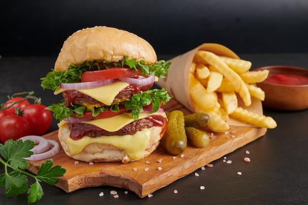 Домашний гамбургер или гамбургер со свежими овощами и сырным салатом и майонезом, картофель фри на кусочках коричневой бумаги на черном каменном столе. концепция быстрого питания и нездоровой пищи