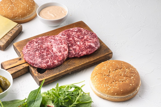 Homemade hamburger. raw beef patties, sesame buns with other ingredients set, on white stone table