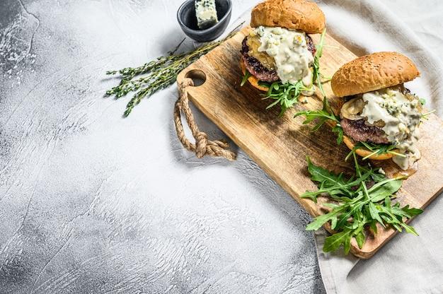 Домашний гамбургер с голубым сыром, мраморной говядиной, луковым мармеладом и рукколой. серый фон вид сверху. копировать пространство