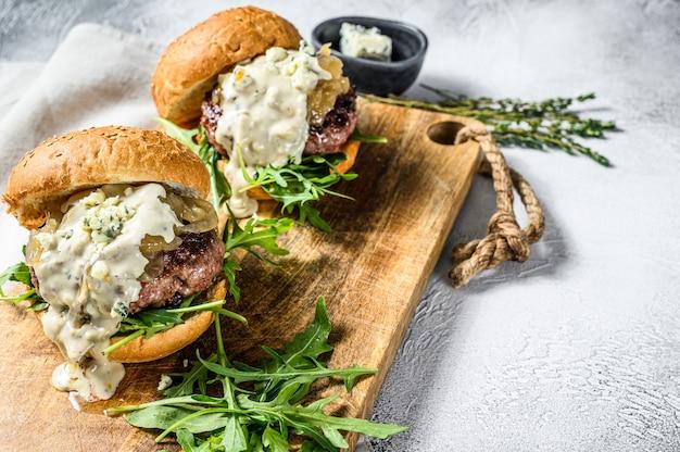 Домашний гамбургер с голубым сыром, мраморной говядиной, луковым мармеладом и рукколой. серая поверхность. вид сверху. копировать пространство