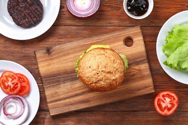 カツレツ、サラダ、玉ねぎ、トマト、チーズの自家製ハンバーガー。チーズバーガー、ハンバーガー。