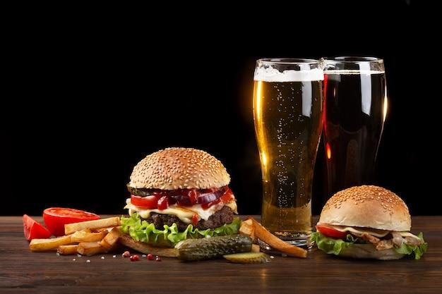 フライドポテトと木製のテーブルにビール2杯の自家製ハンバーガー。暗い背景のファーストフード。