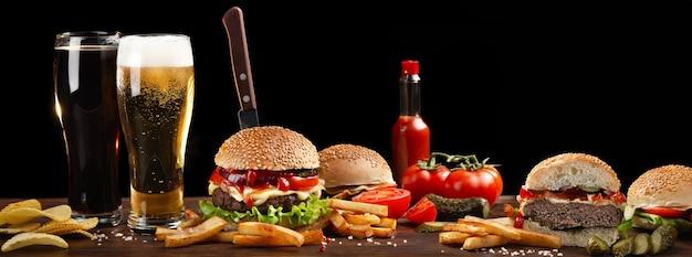 フライドポテトと木製のテーブルにビール2杯の自家製ハンバーガー。ハンバーガーにナイフを刺した。暗い背景のファーストフード。