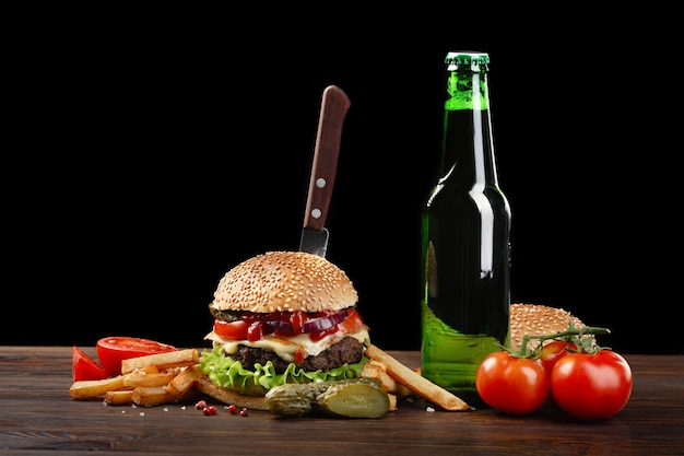 Homemade hamburger with french fries and bottle of beer on wooden table. in the burger stuck a knife. fastfood