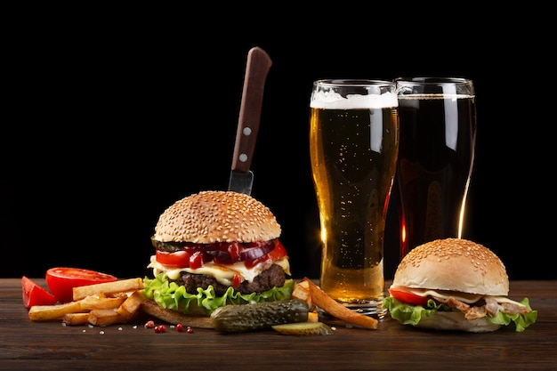 Homemade hamburger with french fries and glasses of beer on wooden table. in the burger stuck a knife