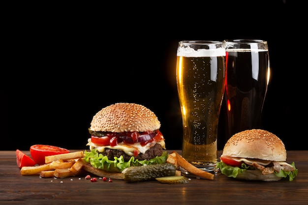 Homemade hamburger with french fries and two glasses of beer on wooden table. fastfood on dark background.
