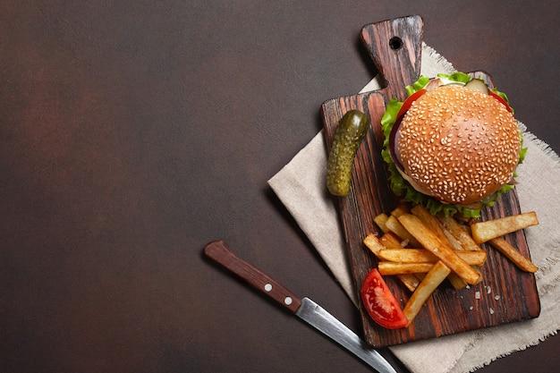 まな板とさびた背景に牛肉、トマト、レタス、チーズ、玉ねぎ、きゅうり、フライドポテトの材料を使った自家製ハンバーガー。テキストの場所を含む上面図。