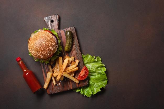 まな板とさびた背景に牛肉、トマト、レタス、チーズ、玉ねぎ、きゅうり、フライドポテトの材料を使った自家製ハンバーガー。上面図。