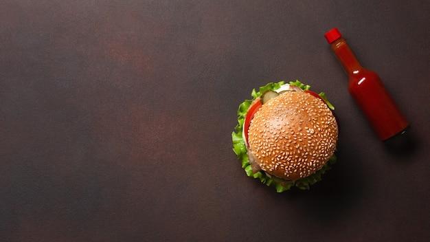さびた背景に牛肉、トマト、レタス、チーズ、玉ねぎ、きゅうり、フライドポテトを使った自家製ハンバーガー。上面図。