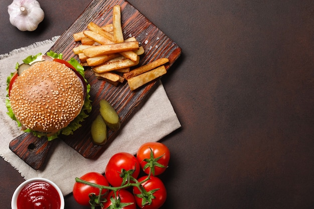 Homemade hamburger with ingredients beef, tomatos, lettuce, cheese, onion, cucumbers and french fries on cutting board and rusty background. top view with place for your text.