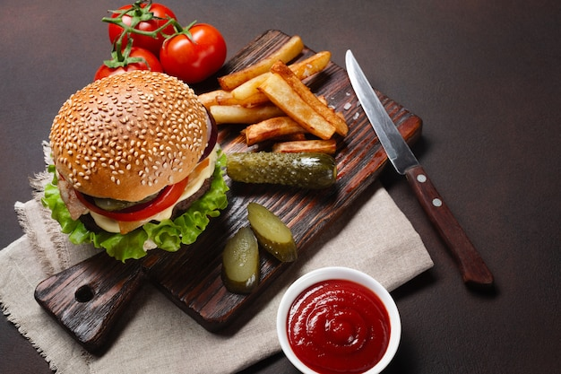 Homemade hamburger with ingredients beef, tomatos, lettuce, cheese, onion, cucumbers and french fries