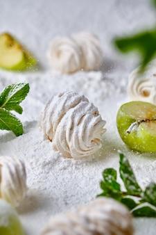 Домашний яблочный зефир ручной работы на фоне сахарной пудры. десерт на снегу. сладость украшена яблоками и мятой.