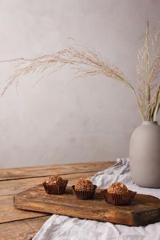 灰色のテーブルクロスと素朴な木製のテーブルに自家製の手作りのお菓子やキャンディー。自家製ヘルシースイーツ、美味しいデザート、ナチュラルスイーツ、キャンディー。