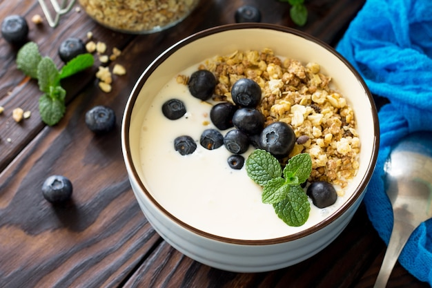 Homemade healthy breakfast in a bowl with homemade baked granola fresh blueberries and yogurt