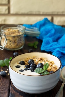 Homemade healthy breakfast in a bowl with homemade baked granola fresh blueberries