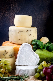 Homemade healthy cheese products stack and grapes on dark background