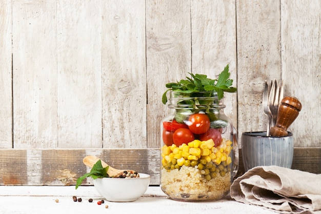 Homemade healthy layer salad in mason jar on a wooden background